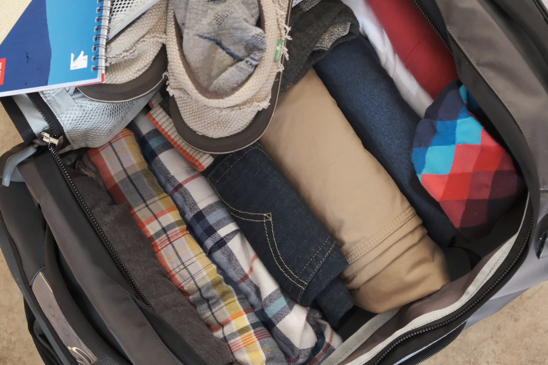 A luggage bag is packed full with pants, shirts, shoes and socks. Photo by Brandon Mathis.