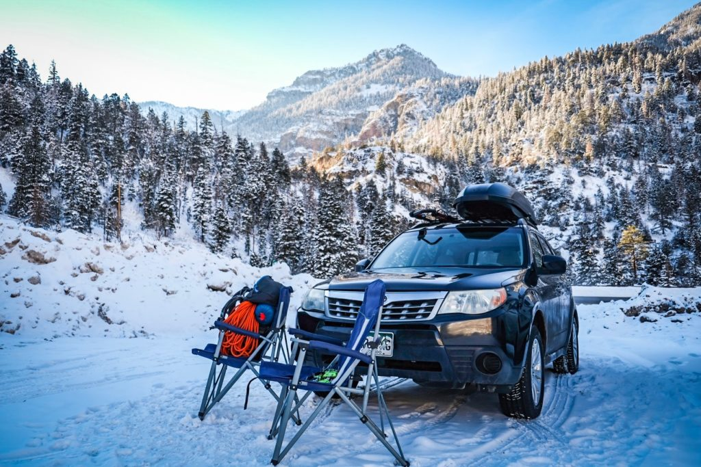 Two camp chairs are set up in front of a car parked near the Ouray Ice Park.