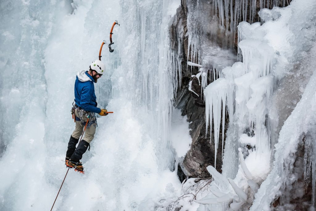 An ice climber stops to place a screw at the Ouray Ice Park.